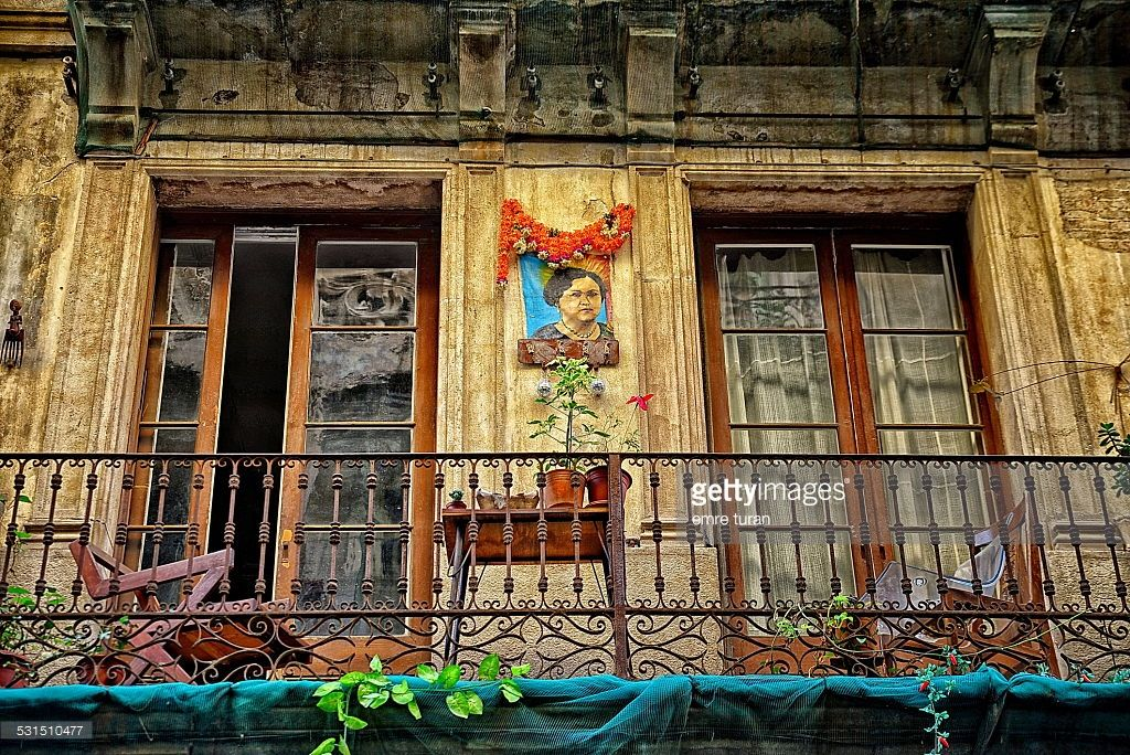an old apartments 1st floor balcony with 2 chairs, small table, flower pots and a woman portrait.