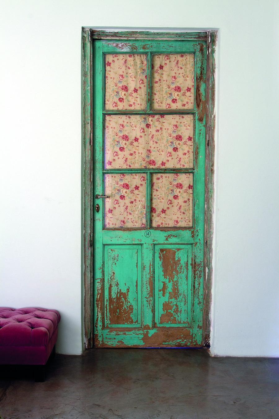 Desde el cuarto, una clásica puerta antigua con tablero y vidrio repartido comunica con el baño en suite. Fue lijada y patinada  manteniendo su espíritu vintage, y para ganar privacidad, la dueña  de casa le hizo un visillo con un retazo de tela floreada.
