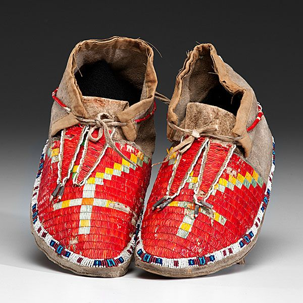 Sioux Beaded and Quilled Hide Moccasins, thread and sinew-sewn with a single lane of beadwork around soles in white, red white-heart, dark blue, and light blue; vamps quilled with red, green, and yellow cross design; tongues quilled and edge beaded, length 10.5 in. ca 1900