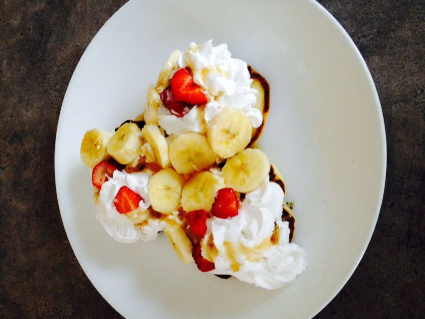 Pancakes with whipped cream, bananas, strawberries, and a drizzle of syrup on top!