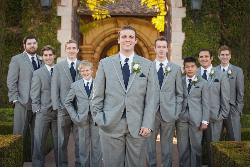 The Groom And Groomsmen Wearing Light Gray Tuxedos With Navy Blue Vests Ties