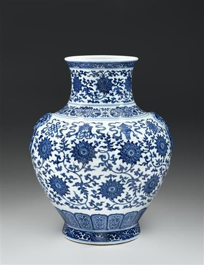 "Large and important Chinese blue and white Ming-style vase,  Qianlong seal mark and of the period.  The robust hu-form vase decorated to ovoid body with chrysanthemum scrolls and blossoms enclosing shou symbols below the eight auspicious Buddhist emblems; neck adorned with further foliate scrolling and a wave band at rim;  with twin molded ring and mask handles; rich cobalt blue applied to imitate Ming ""heaping and piling"" effect. #FreemansAuction"