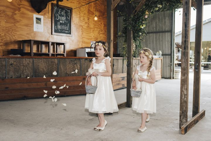 Flower girls in white dresses and white and gold ballets | itakeyou.co.uk #wedding #rustic #rusticwedding #barnwedding #vineyardwedding #realwedding #weddingphotos