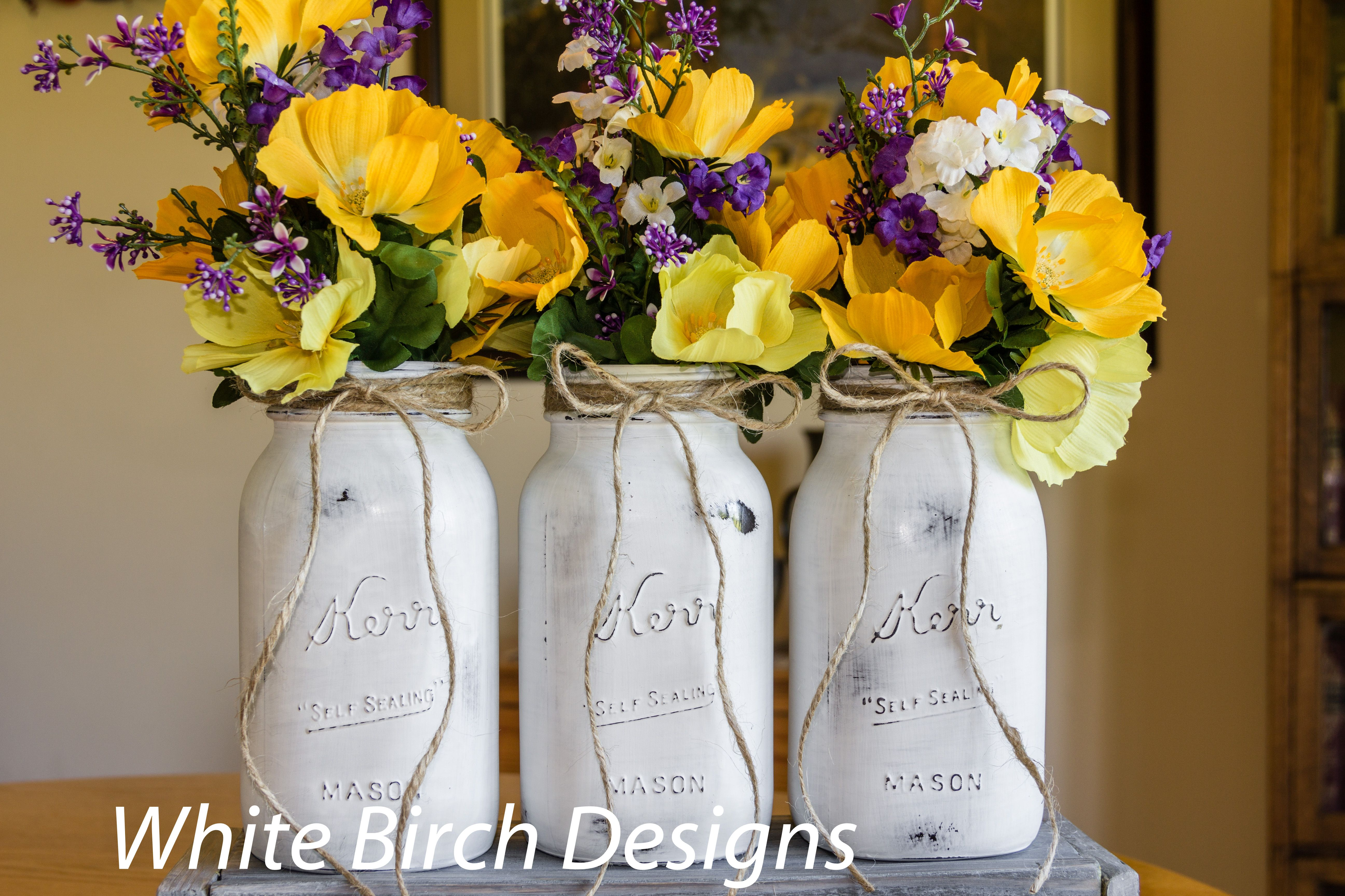 Pure white mason jars with distressing have full bouquets in yellow