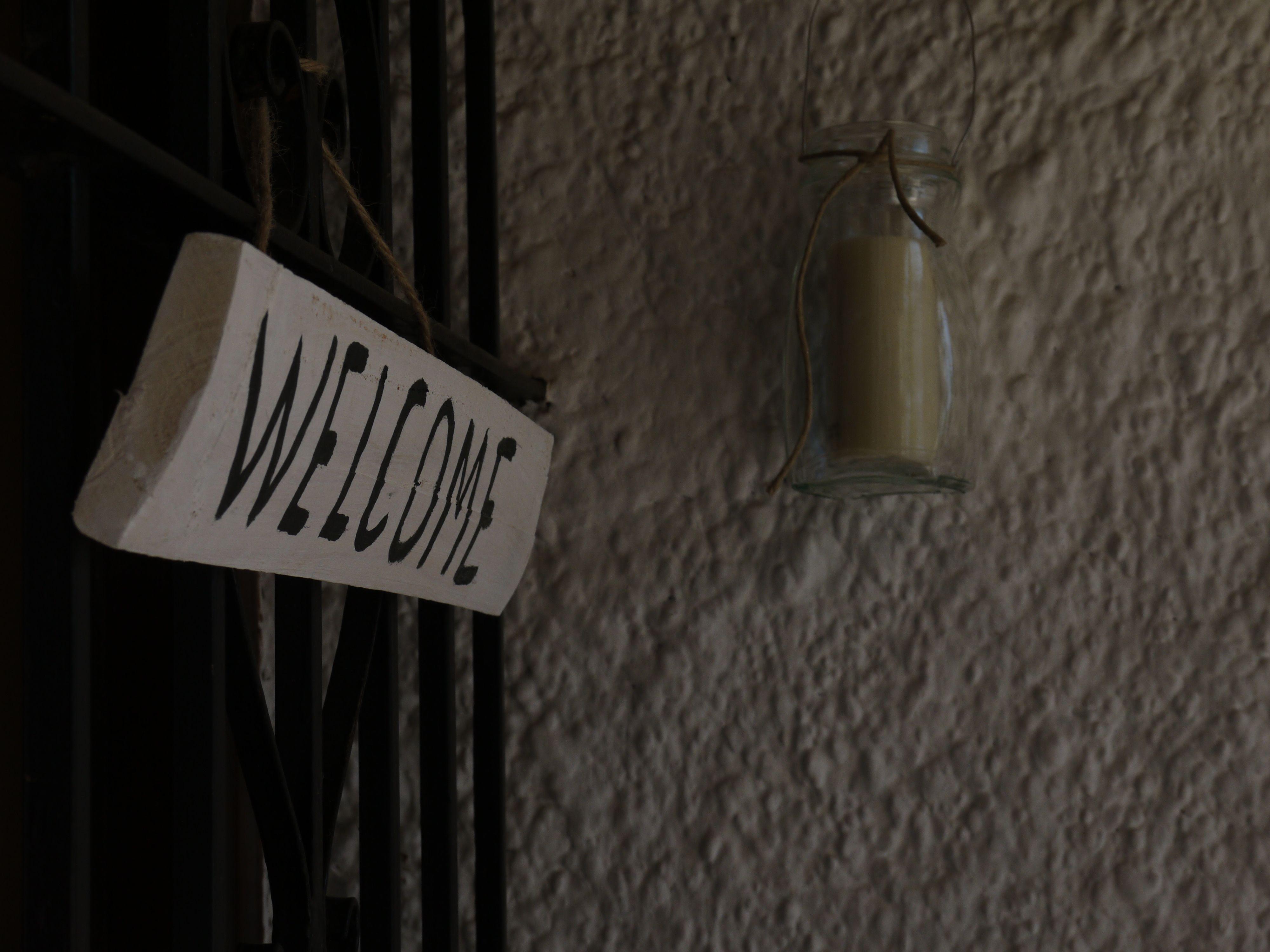 Bienvend@s y Welcome a tod@s.  Letrero pintado a mano hecho de madera de pallet y farolillo de bote de cristal reciclado.