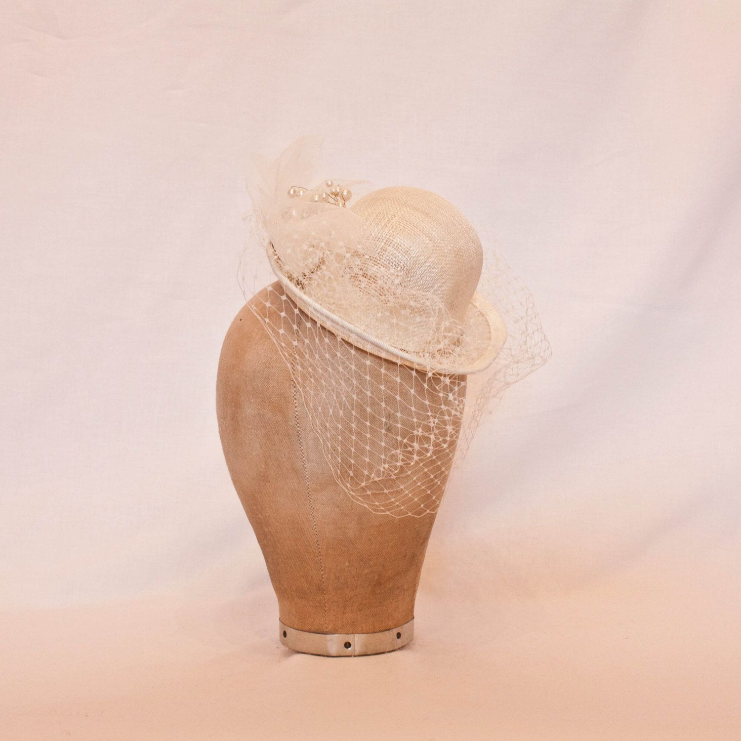 Small ivory bowler hat shaped fascinator with veiling and pearl bead detailing