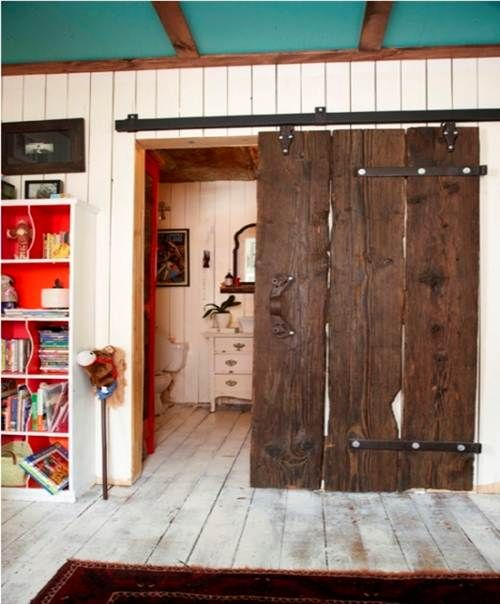 Very rustic sliding barn door with reclaimed wood boards, strap hinges