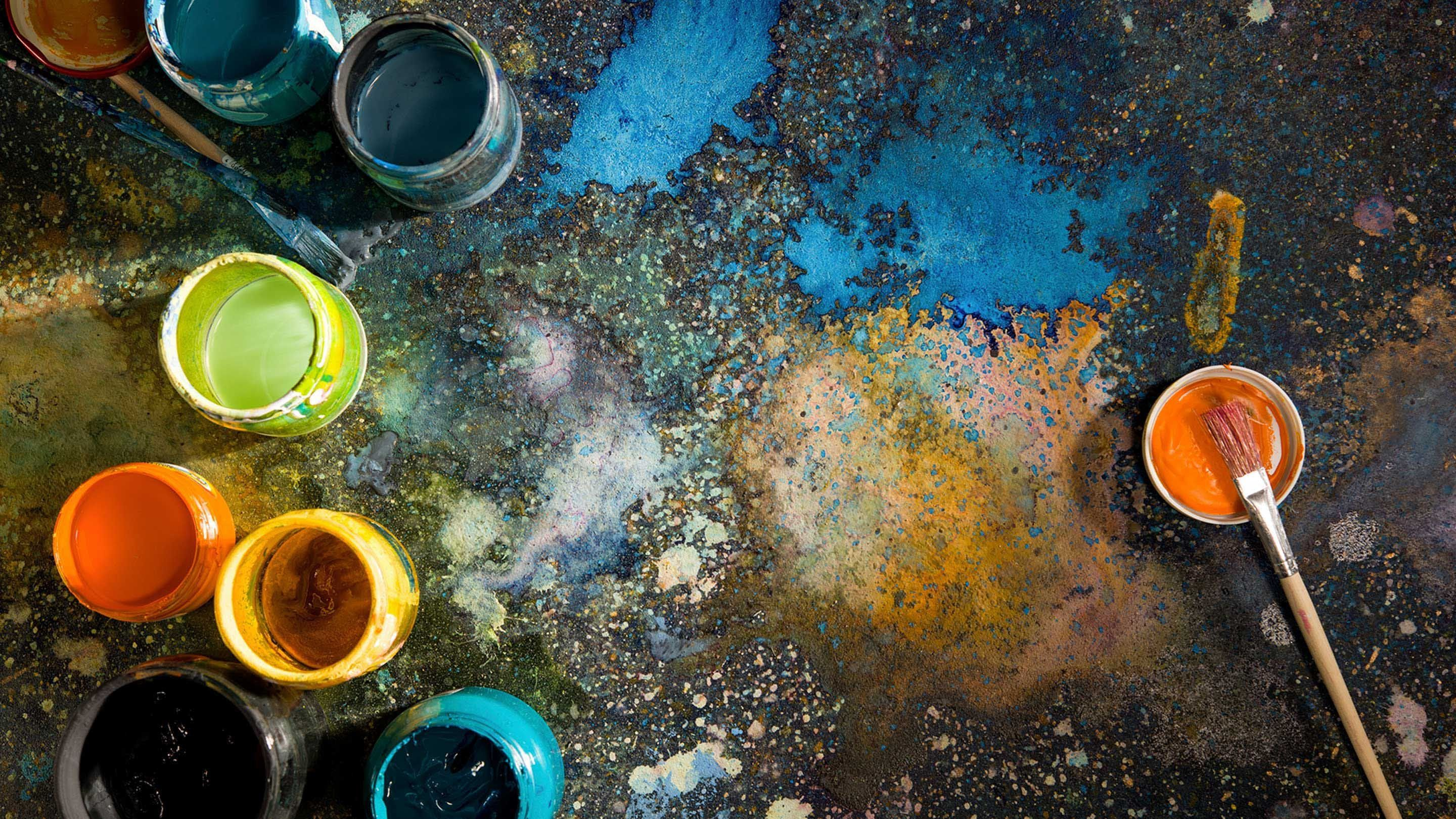 Paint brushes and jars of paint are on a black floor splattered with colorful paint.