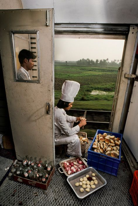 Meals for traveling passengers - Peeling onions in a moving train  Steve McCurry - India. 1983