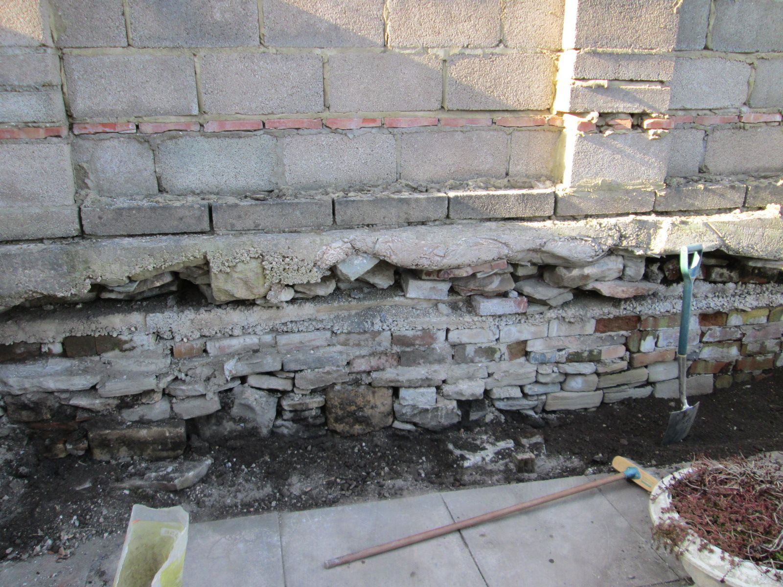 The wall is revealed; a huge pile of stones has been removed and all the cement's gradually being chipped away and taken to the tip.
