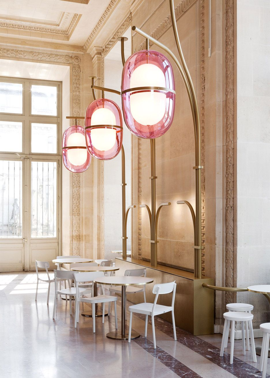 French designer Mathieu Lehanneur has renovated a cafe inside the Louvre in Paris, adding modern pink acrylic light fixtures that contrast with their historical surrounds