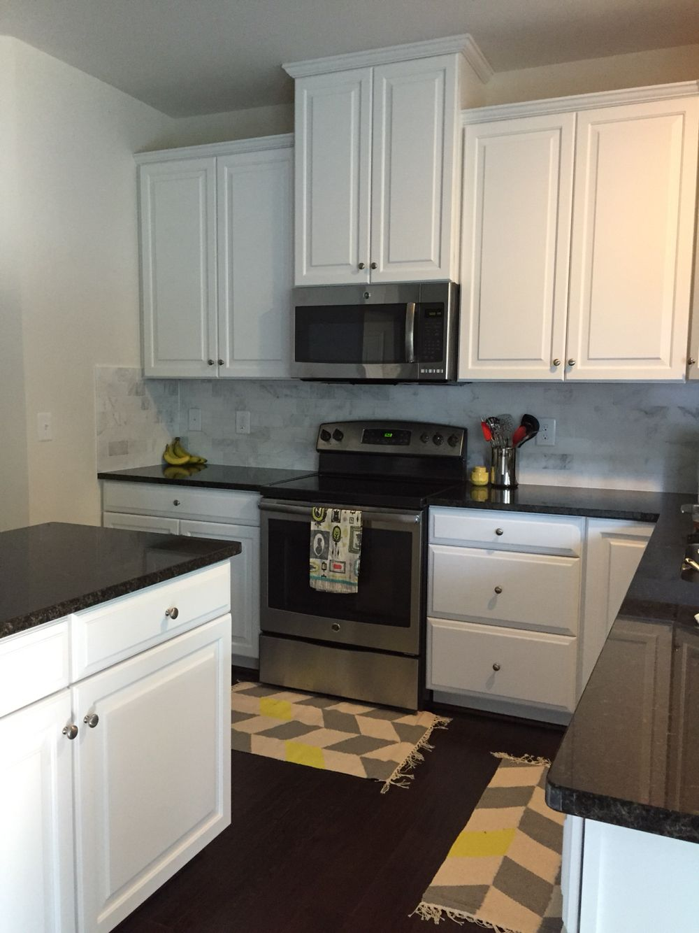Black And White Kitchen With Honed Marble Backsplash And