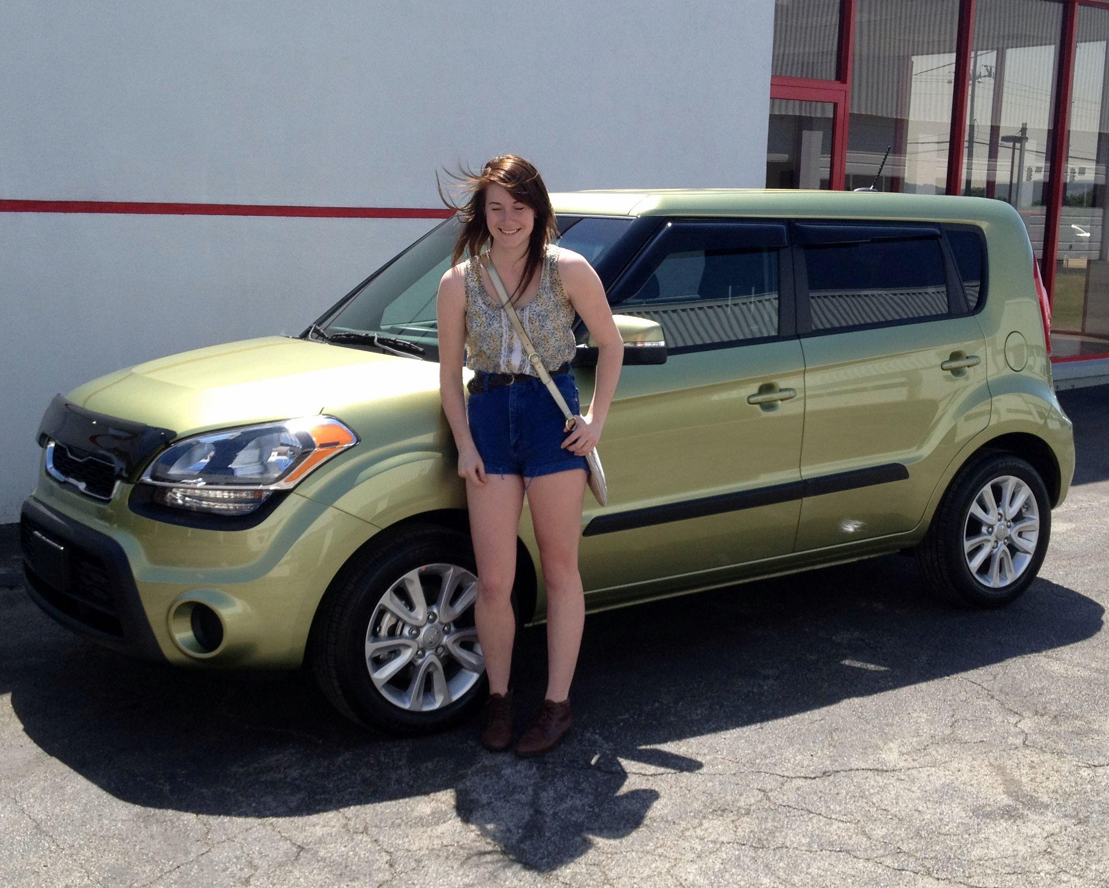 Grace Mills in front of her very first car A 2012 Kia Soul in Alien