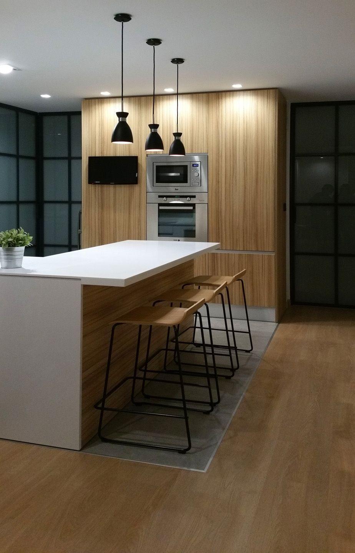 Peninsula de cocina en solid surface. Puertas metálicas lacadas al horno, lámparas vintage. Interiorismo de AZ Diseño.