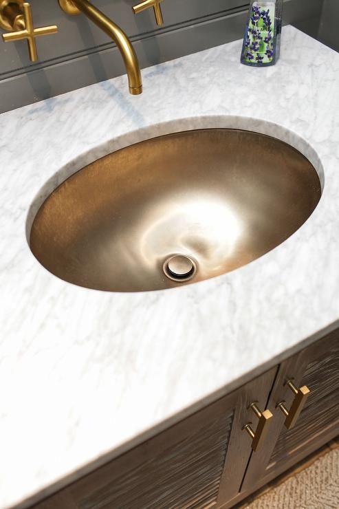 amazing bathroom features a gray oak louvered bath vanity adorned with brass pulls topped with white