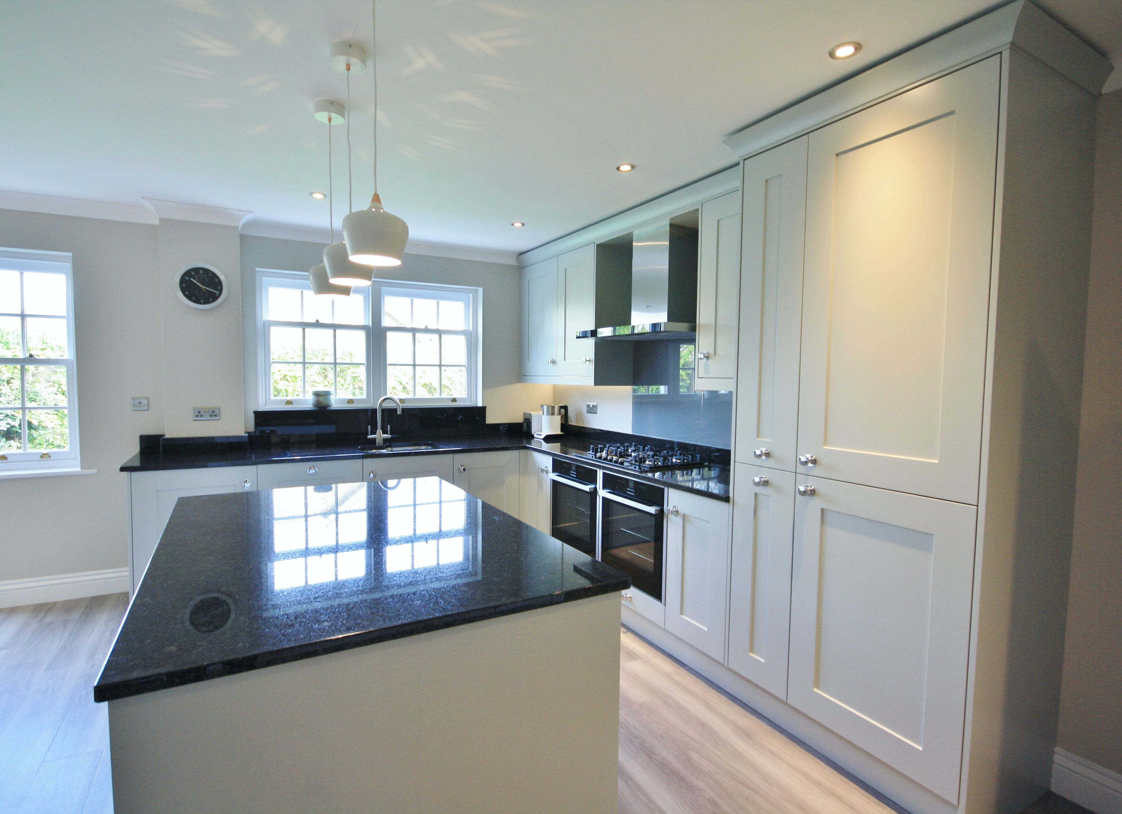 Two window kitchen design  partridge grey units with black granite worktops upstands and