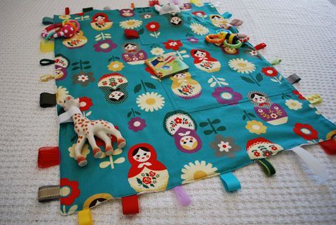 Travel Baby Blanket with Attached Toys Free Sewing Pattern Play blanket with pockets and ribbons...Pockets don't need to have anything in them...It's all in the fabricPlay blanket with pockets and ribbons...Pockets don't need to have anything in them...It's all in the fabric