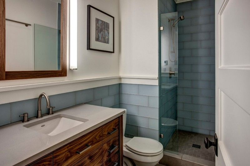 Walk in bathroom design with blue glass tiles walls and dark beige floors white countertop also