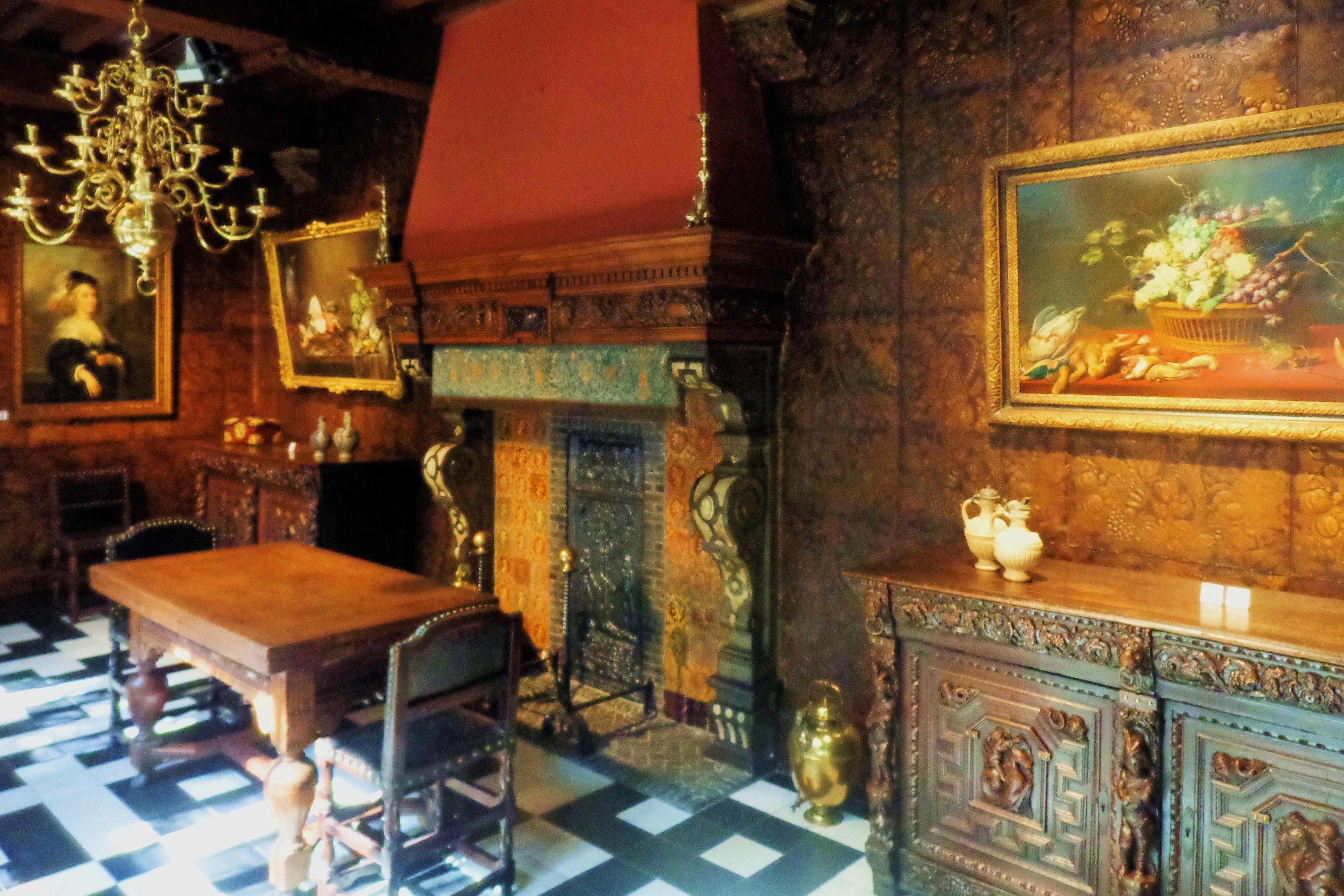 De muren van de eetkamer zijn voorzien van goudleerbehang. aan de