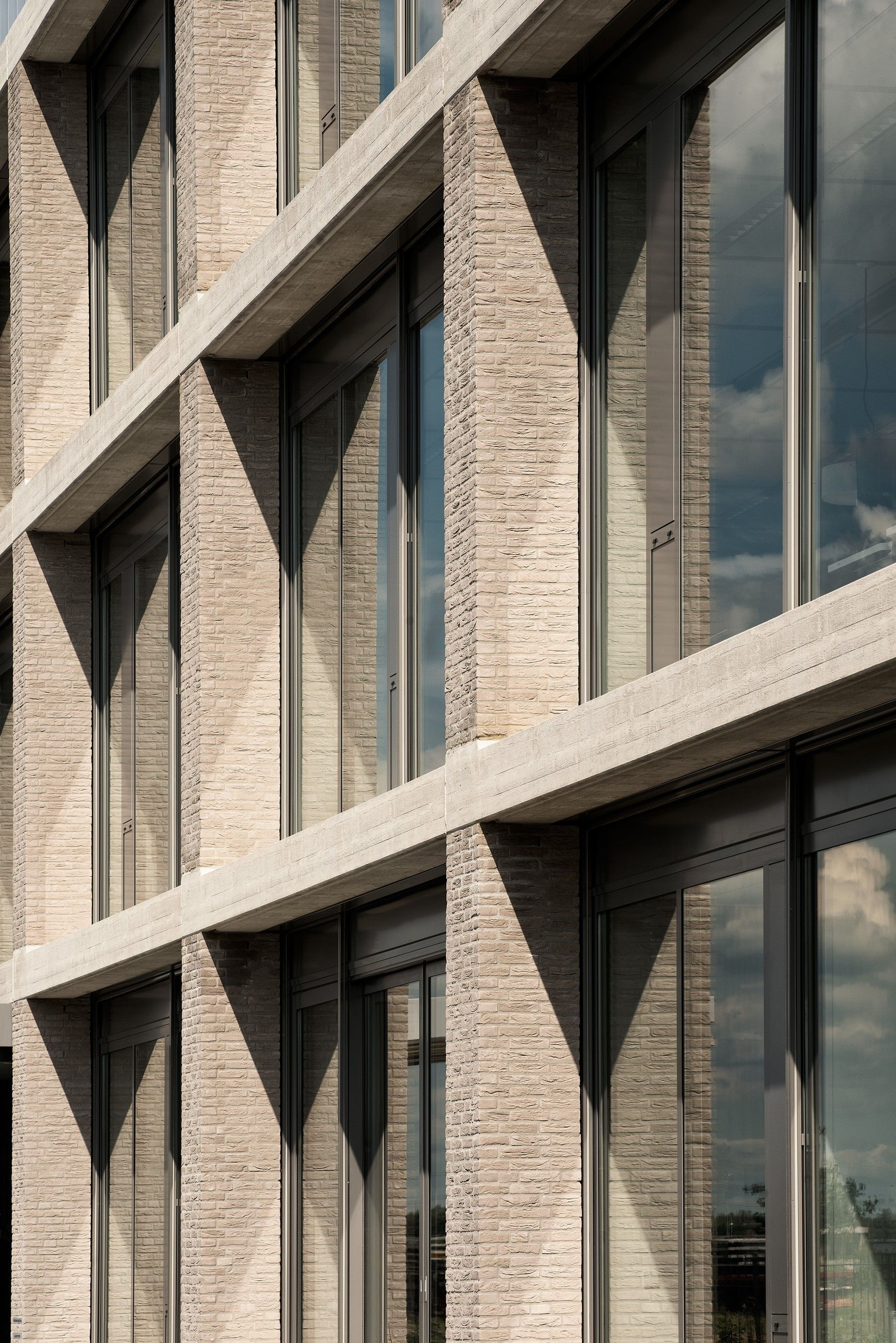 Buff brick rhythmic facade with depth and shadow and for Window design cement