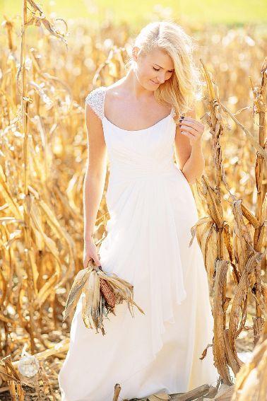 A beautiful bride at rustic barn in cap sleeve wedding dress.