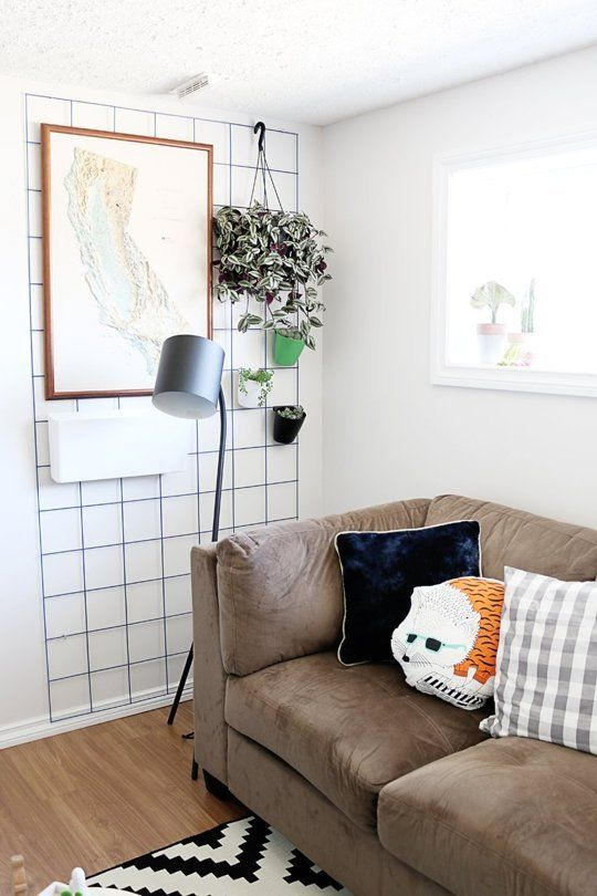 A large wire grad is fastened to the wall here with mug hooks but you could use small clear command hooks to the same effect then hang your art or