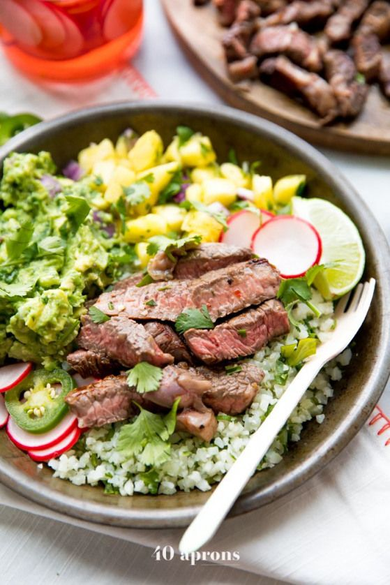 These steak taco bowls are so flavorful with tender steak creamy guac sweet pineapple salsa and cilantrolime cauliflower rice Whole30 paleo and low carb theyre a healthie...