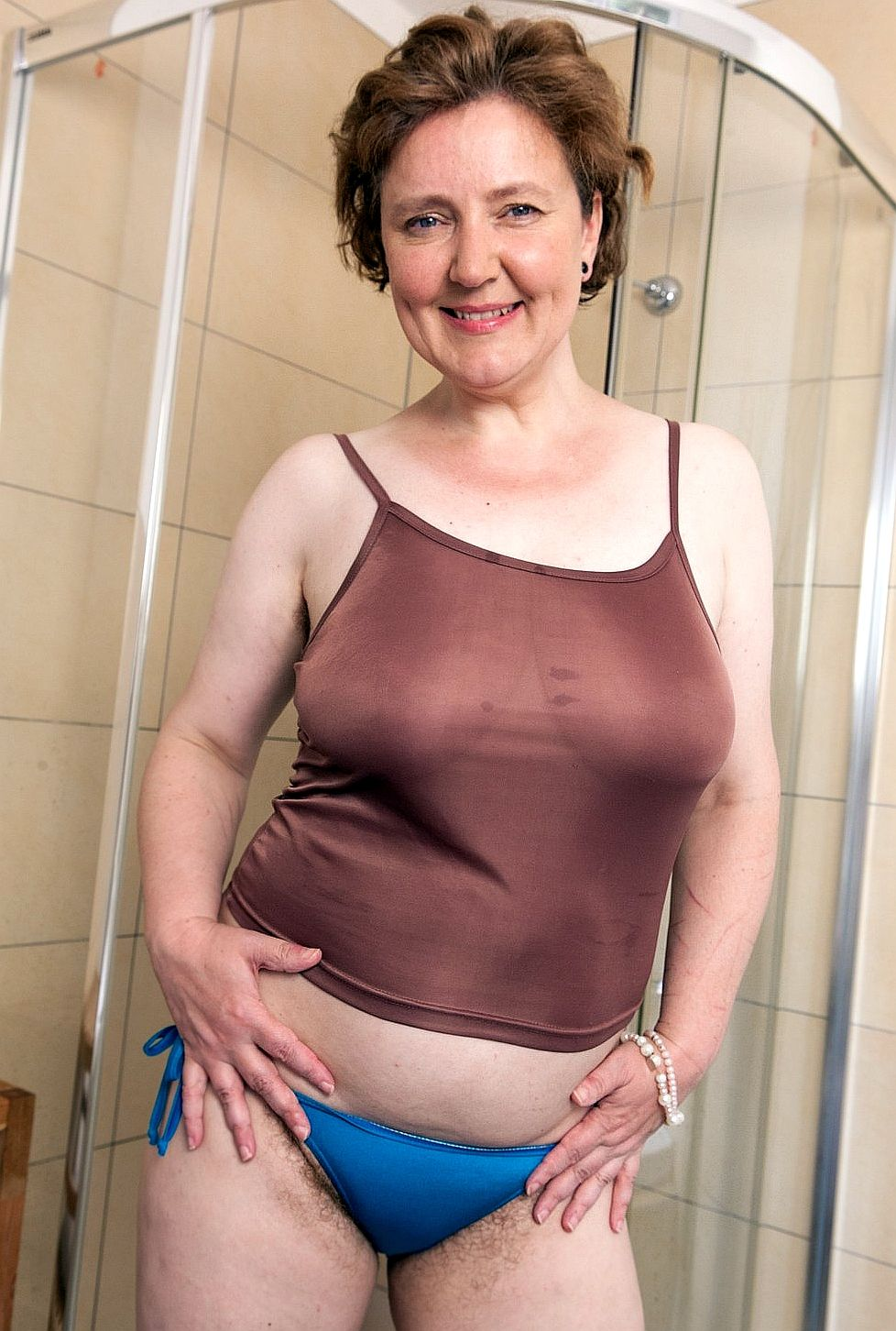 older woman in brown top and blue panties showing pubic hair | older