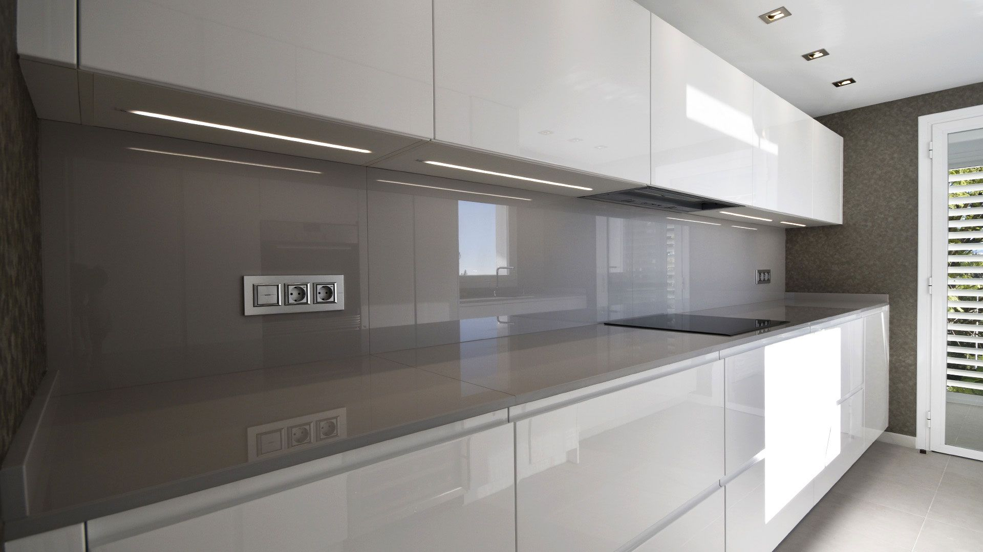 Cocina moderna muebles lacados en blanco alto brillo con for Encimera negra brillo