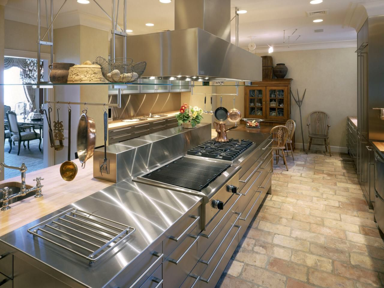 A Unique Kitchen With Stainless Steel Cabinets And Brick Floors The
