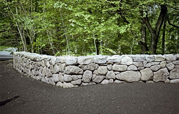 A freestanding mortared fieldstone wall blends strength with the natural look of a dry stack