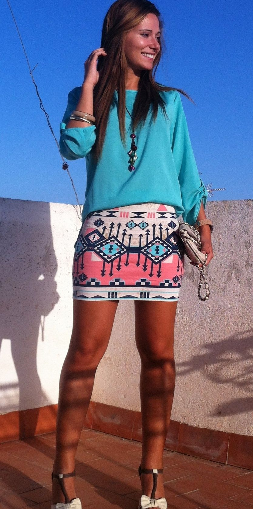 """A cream pink and blue tribal print skirt with a teal long sleeve shirt. Pair this with light brown or cream accessories."""
