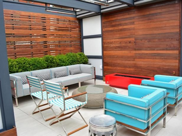 Some homeowners need privacy from neighbors, or want to screen an unwelcome view. In this case, Topiarius designers created an outdoor entertainment and lounging area, and used horizontal slats, made from oiled Ipe, to block the sight of a back alley. Solid, white Plexiglas panels were also installed; Jenkins-Sutton says they were less expensive and easier to cut than glass. The painted cedar pergola has hidden heaters to provide warmth on chilly days. This space uses pedestal porcelain…