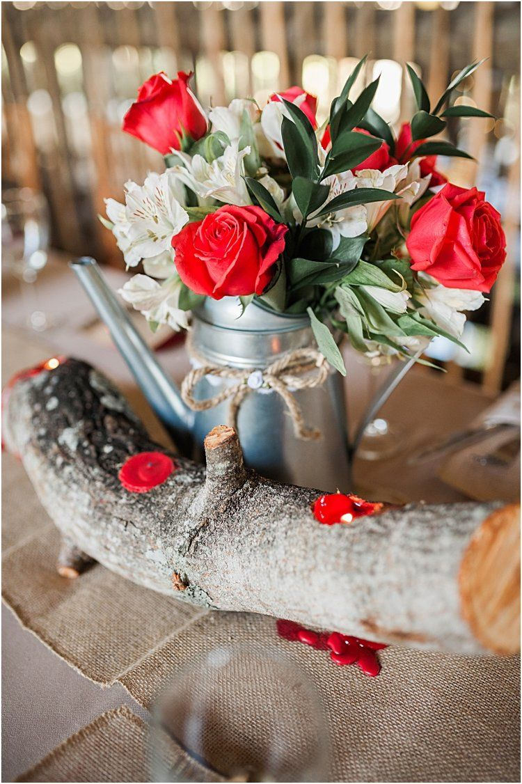 log centerpiece and red roses at outdoor rustic wedding at schneblys ...