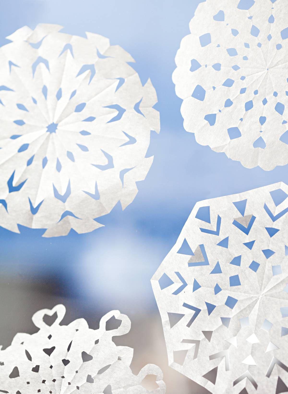 Lapset ovat leikanneet silkkipaperista lumihiutaleita.