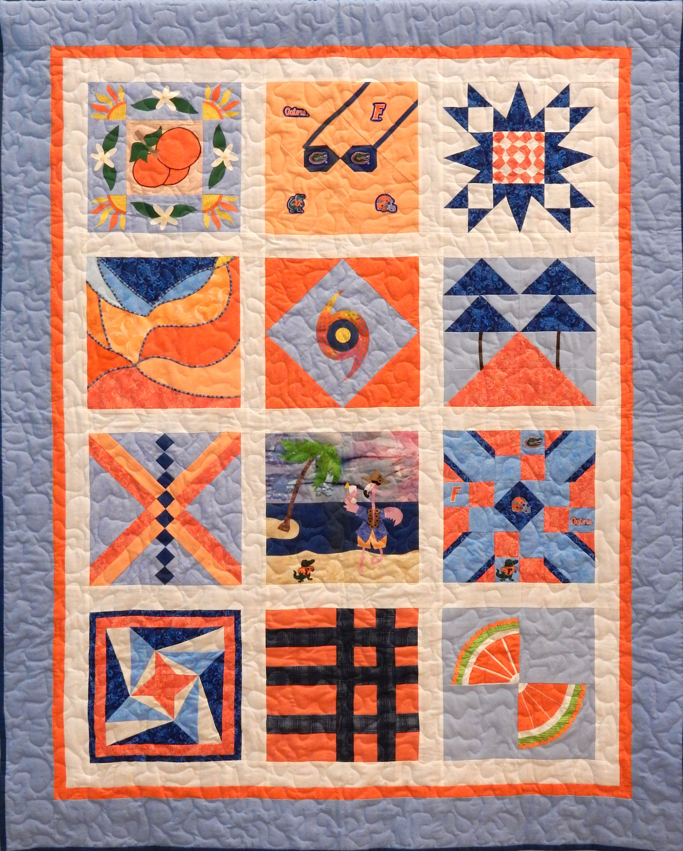 "Road to the Florida Swamp Lap Quilt 05 ""The Florida Swamp is located in Gainesville, Florida, and is home to the University of Florida Gators. Each block was designed by a member of Quilters Unlimited (See quilt label) in a 2013 Road to Florida challenge. I decided to make the blocks in my alma mater's colors, orange and blue."""