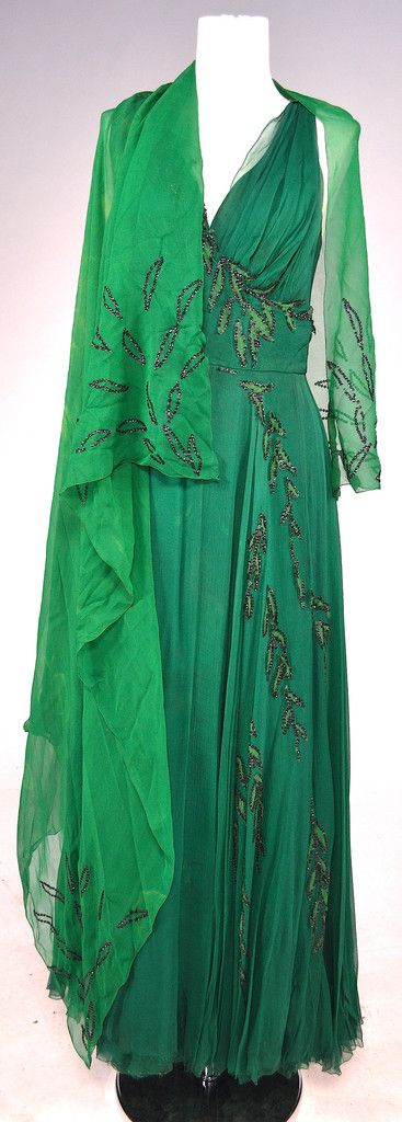 """Shirley Booth """"Mrs. Vivien Leslie"""" green dress designed by Edith Head from About Mrs. Leslie (Paramount, 1954) Emerald green chiffon sleeveless evening gown with kelly green leave appliques trimmed in black sequins along bodice, front and shoulders.  Hook  eye with zip back closure.  Paramount label handwritten """"Shirley Booth"""".  Coordinating scarf.  Chiffon is fraying along edges.  Some sequin and applique loss.  Staining along armpits.  Scarf exhibits yellow stains.  Designed by Edith Head."""