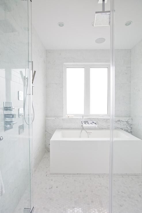 A Large Square Modern Bathtub Sits In A Large Seamless Glass Shower And Is Paired Wit Bathroom Tub Shower Combo House Bathroom Designs White Marble Shower Tile