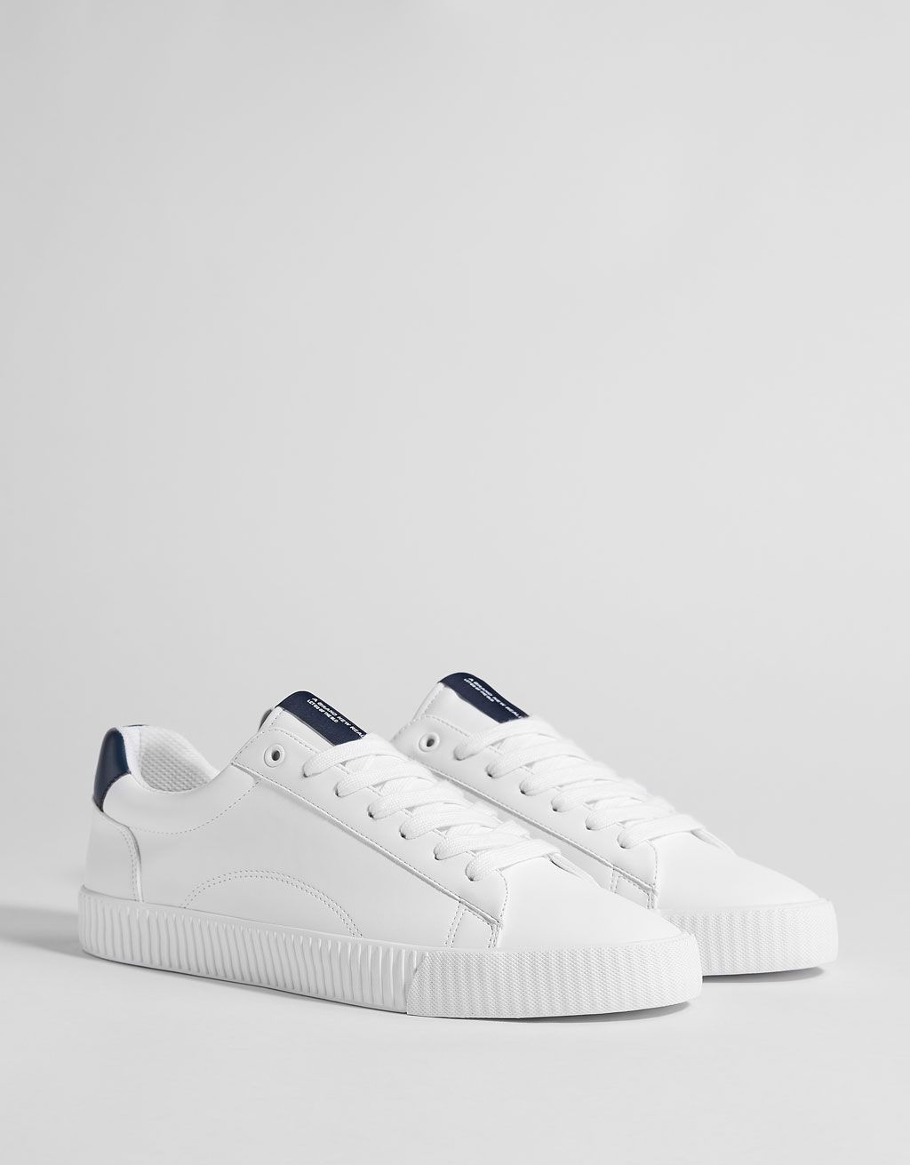 Men's contrasting trainers is part of Shoes - White laceup trainers featuring a sloganprinted blue piece on the tongue and heel, striped white soles and multicoloured slogan detailing on the insoles