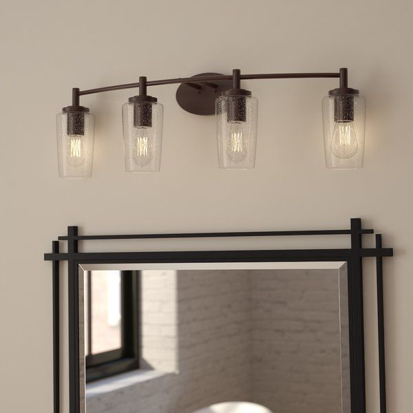 Seeded glass shades pair with edison bulbs to round out this bronze hued vanity light use it to add a traditional touch to the master bath or to round out