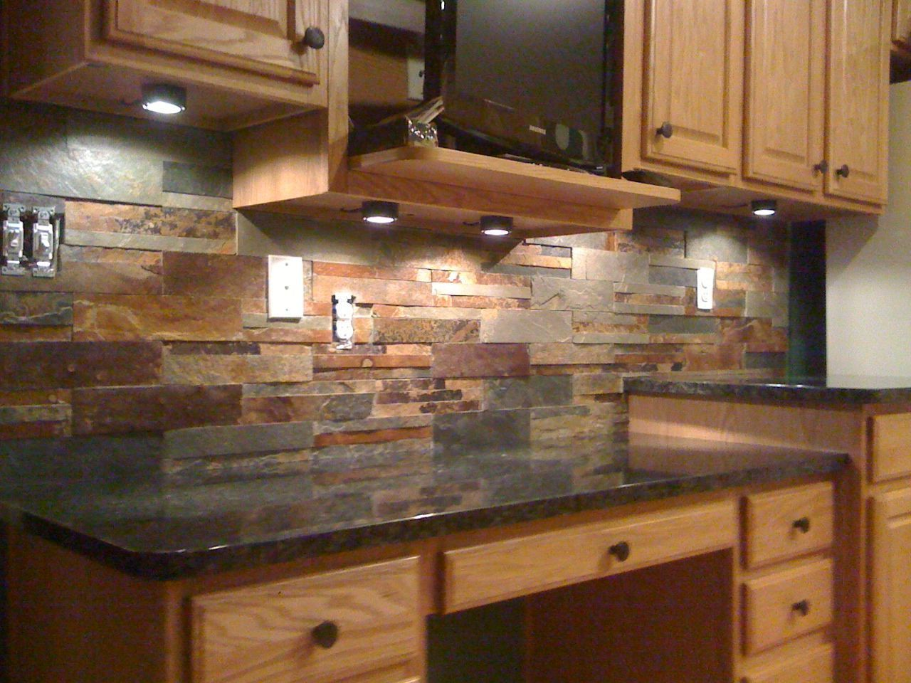 This natural slate tile backsplash is shown with uba tuba for Black kitchen backsplash