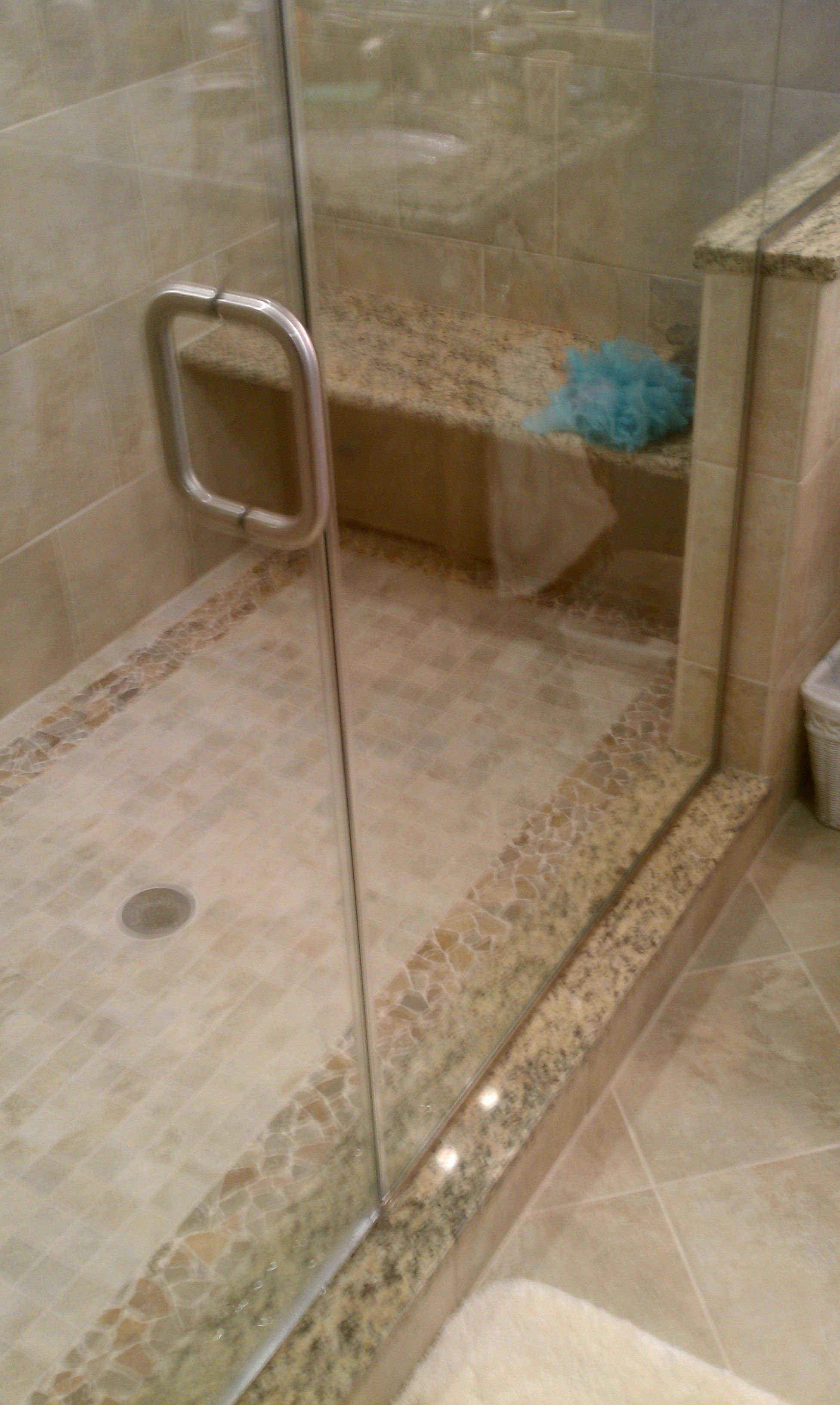 Seamless glass shower doors granite bench in custom shower with boarder tile bathroom Bathroom tile showers