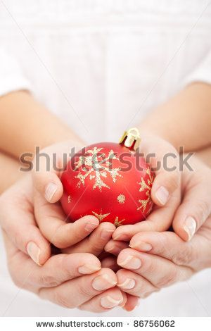 Christmas together concept with child and adult hands holding bauble - stock photo