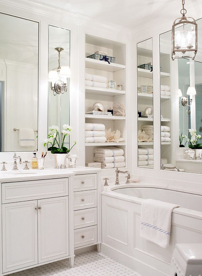 Small, White Bathroom With Mirrors