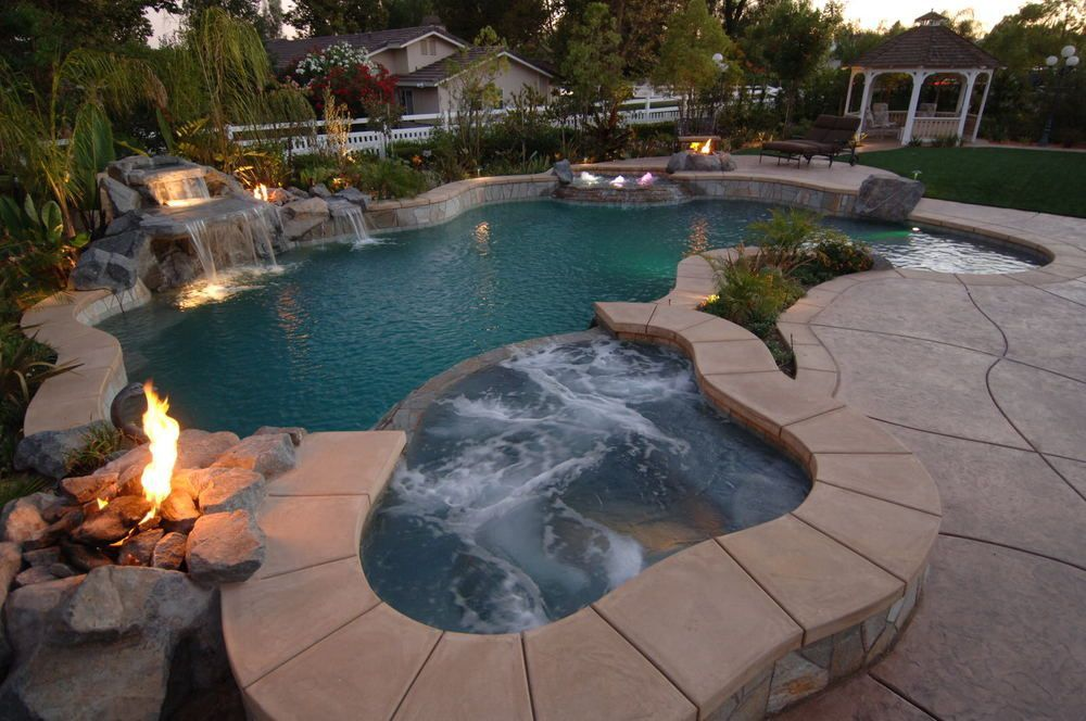 Tropical inground pool with a hot tub and waterfall
