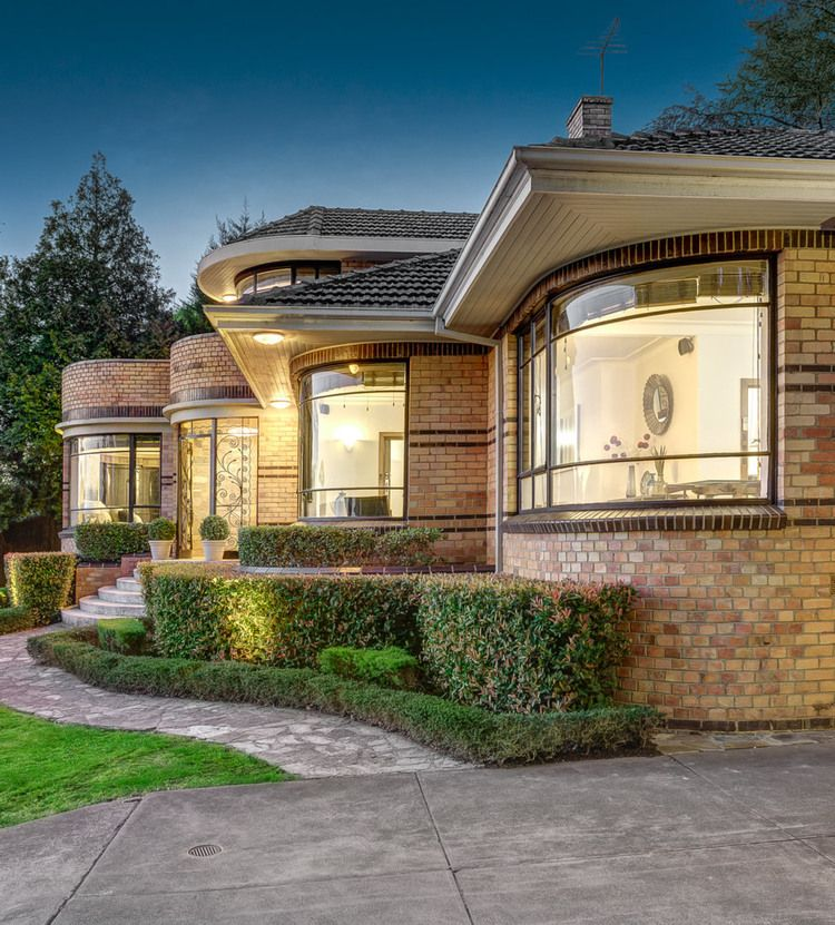 The glazed brown bricks on the window sills, the top & base of the walls, and a repeated double band through the centre of the windows are typical of the Waterfall Style in Australian domestic architecture.