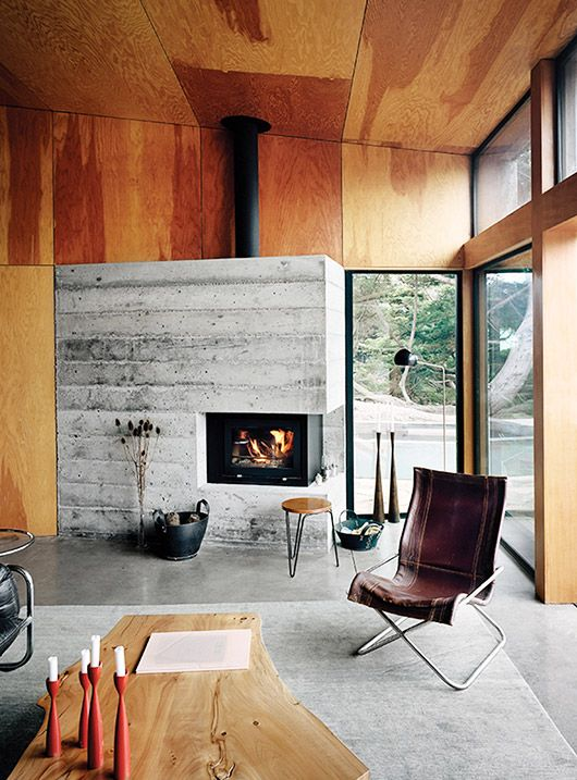Modern cabin with plywood walls and concrete fire place for Beach cabin decor