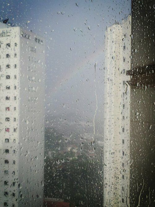 View of buildings & a rainbow thru  glass with raindrops on it