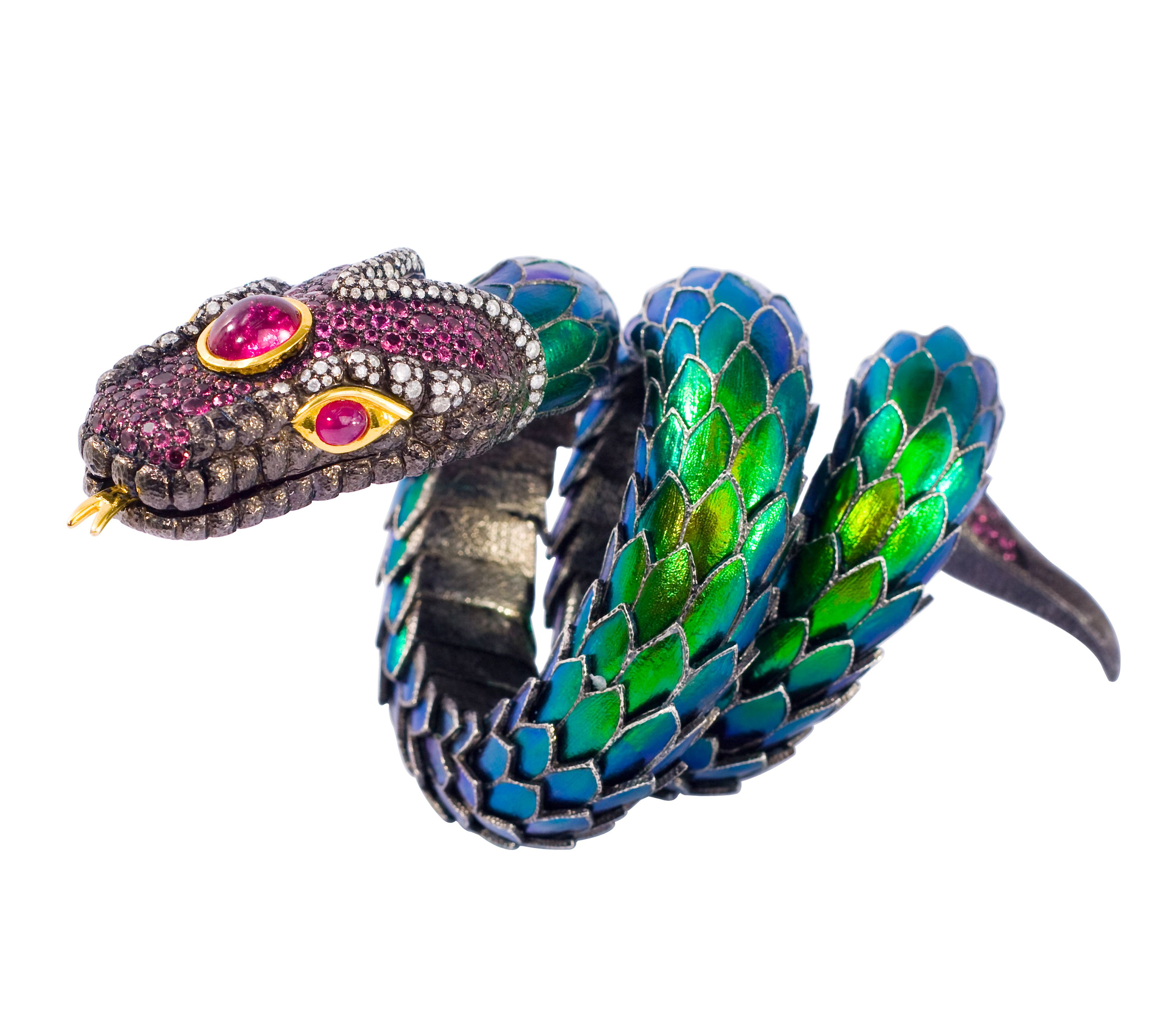 Adoring the beauty of nature, Lotus Arts de Vivre turns the natural into this unique snake design by covering  the body with scarab wings. The head is made of sterling silver enhanced with Iced diamonds, pink tourmalines and rubies for eyes mounted in 18K gold.  Iced diamonds are very popular internationally.They are opaque and LAdV travels far to select the best for their creations.