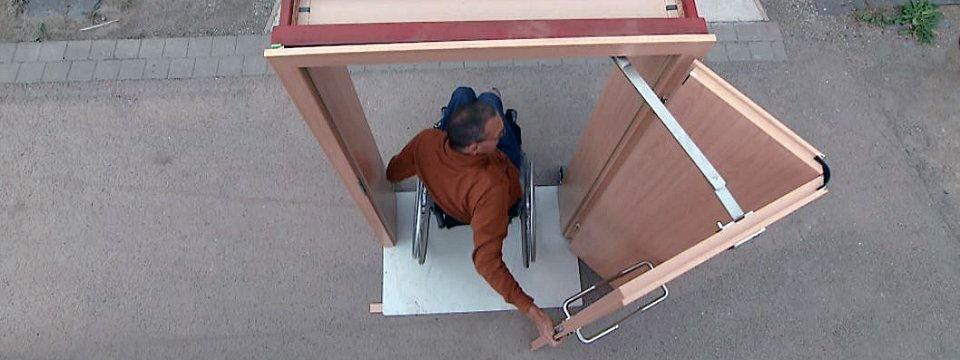 """""""Einfach genial"""", Erfindungen, Innovationen, Neuheiten, mdr-Doku, Blick von oben auf einen Mann im Rollstuhl, der an einem Demonstrationsobjekt im Freien vorführt, wie eine rollstuhlfahrerfreundliche Tür funktionieren kann.    Bildrechte: MITTELDEUTSCHER RUNDFUNK"""